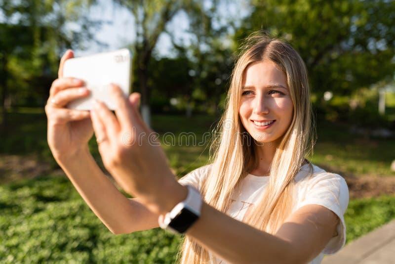 Mooie jonge vrouw met blondehaar die mobiele telefoon met behulp van openlucht Modieus meisje die selfie maken royalty-vrije stock foto
