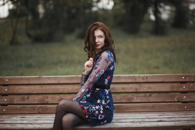 Mooie jonge vrouw met bruine krullende haarzitting op houten bank in de herfstpark Zij die haar haar en het glimlachen houden royalty-vrije stock afbeeldingen