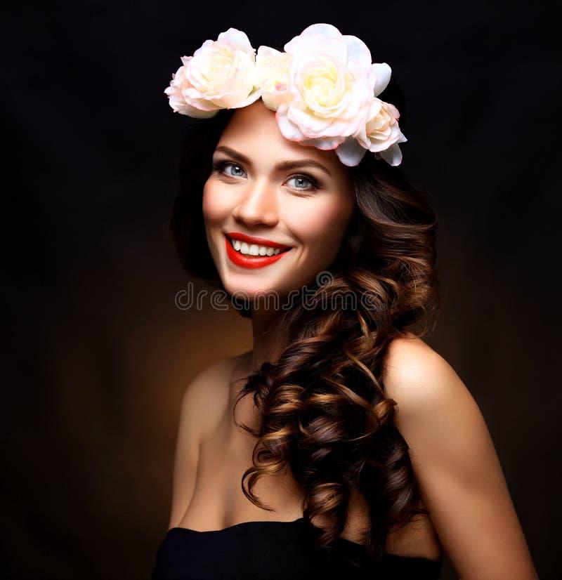Mooie Jonge Vrouw met de Zomer Roze Bloemen Het lange Krullende Haar van Permed en Maniermake-up Het meisje van de schoonheid met stock foto's