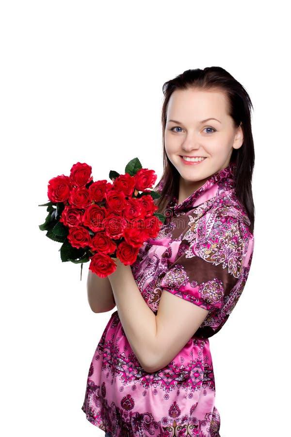Mooie jonge vrouw met een boeket van rode rozen royalty-vrije stock afbeelding