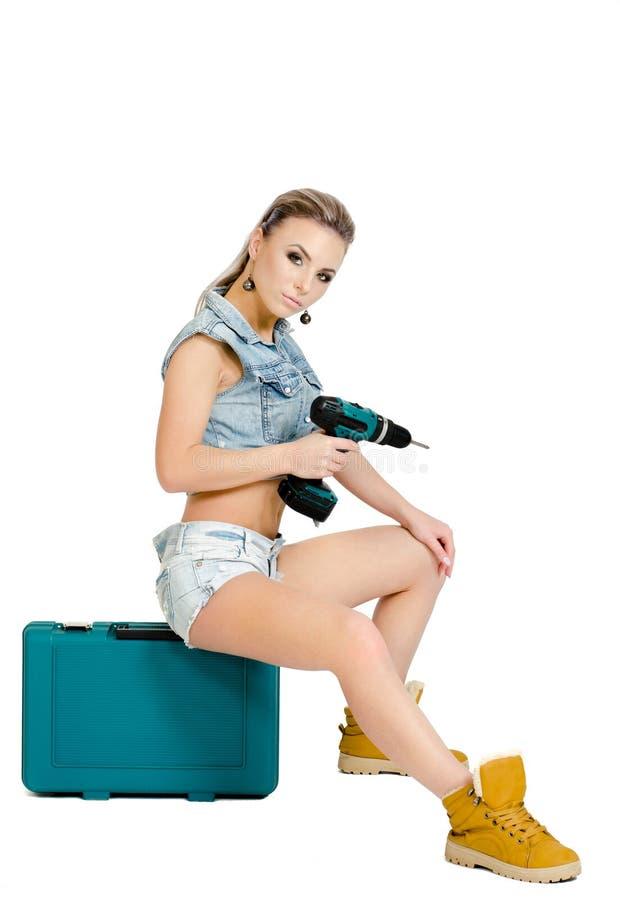 Mooie jonge vrouw met een elektrische schroevedraaier stock afbeelding