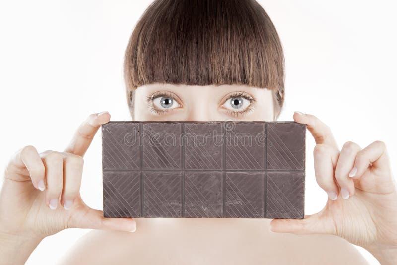 Mooie jonge vrouw met een grote chocoladereep - (Reeks) stock fotografie