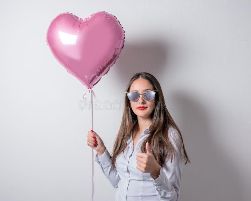 Mooie jonge vrouw met een hart gevormde ballon op een heldere achtergrond De dagconcept van de valentijnskaart ` s royalty-vrije stock foto's