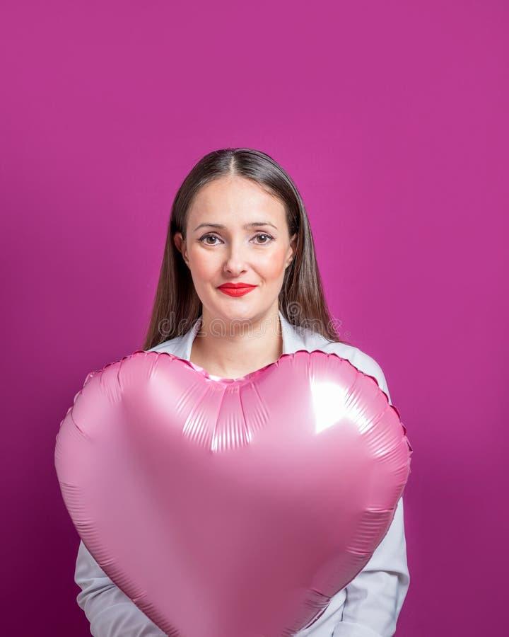 Mooie jonge vrouw met een hart gevormde ballon op een heldere achtergrond De dagconcept van de valentijnskaart ` s stock afbeelding
