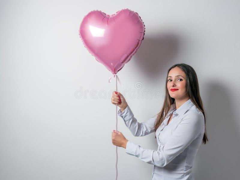 Mooie jonge vrouw met een hart gevormde ballon op een heldere achtergrond De dagconcept van de valentijnskaart ` s royalty-vrije stock afbeelding