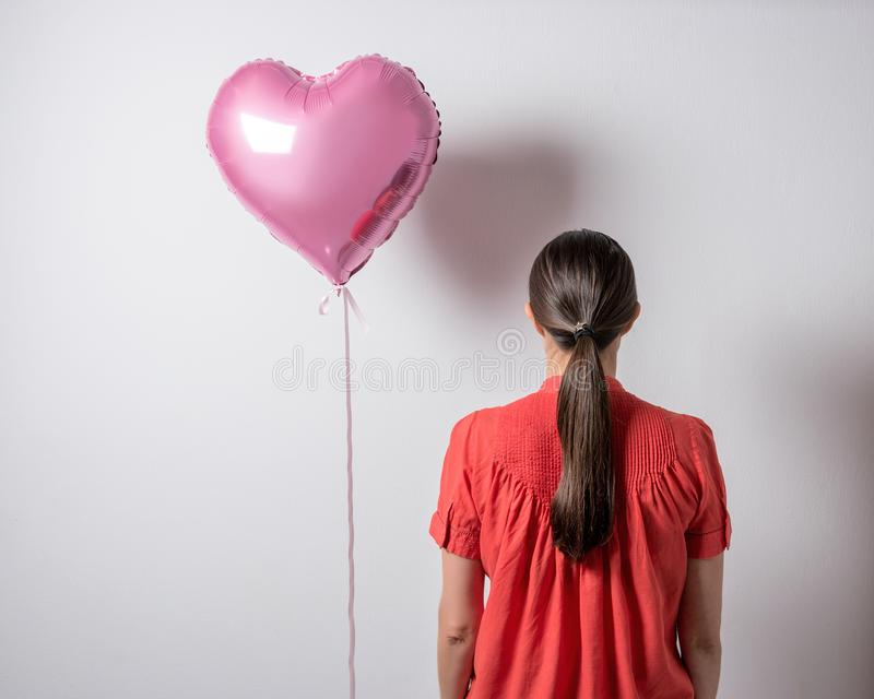 Mooie jonge vrouw met een hart gevormde ballon op een heldere achtergrond De dagconcept van de valentijnskaart ` s royalty-vrije stock afbeeldingen