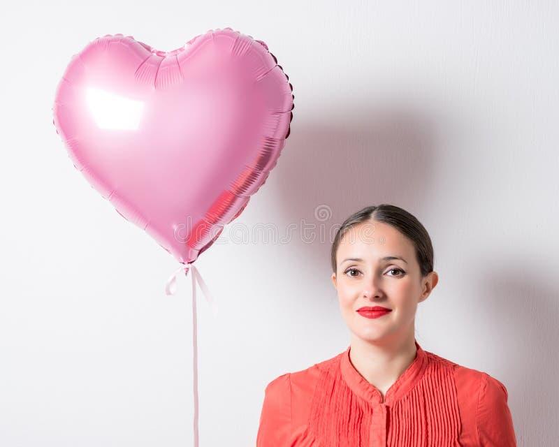 Mooie jonge vrouw met een hart gevormde ballon op een heldere achtergrond De dagconcept van de valentijnskaart ` s stock foto