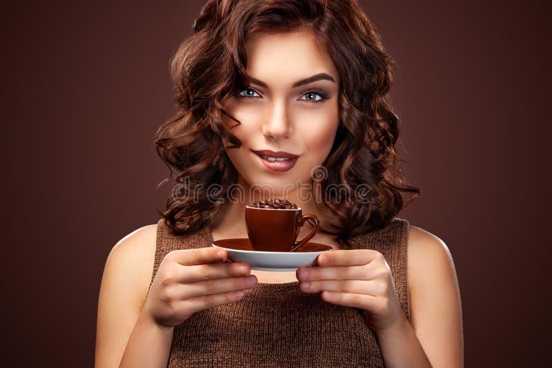 Mooie jonge vrouw met een kop van koffie op de donkere achtergrond stock afbeeldingen