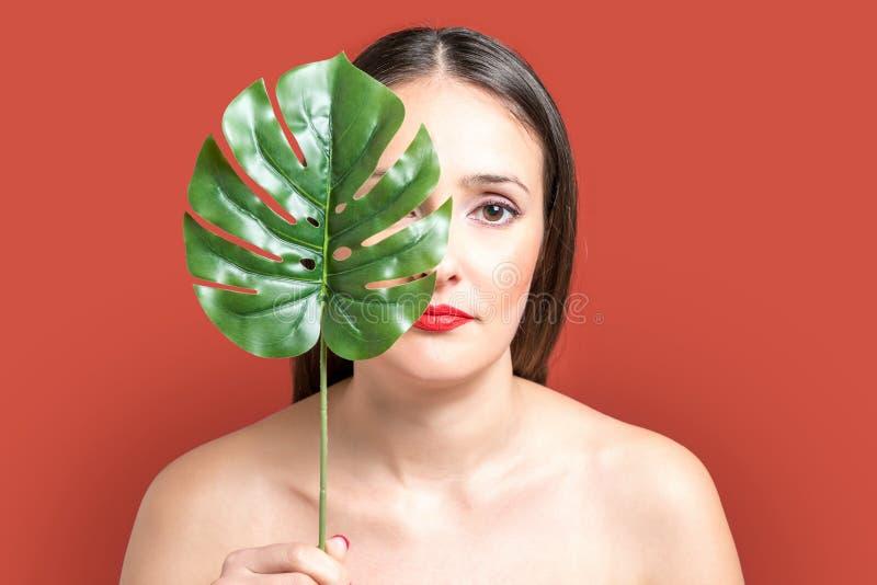 Mooie jonge vrouw met een palmblad op een heldere achtergrond royalty-vrije stock fotografie