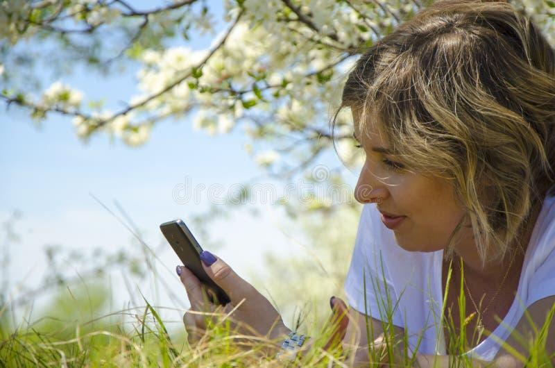 Mooie jonge vrouw met een telefoon, die op het gebied, het groene gras en de bloemen liggen Geniet in openlucht van Aard Het gezo stock afbeeldingen
