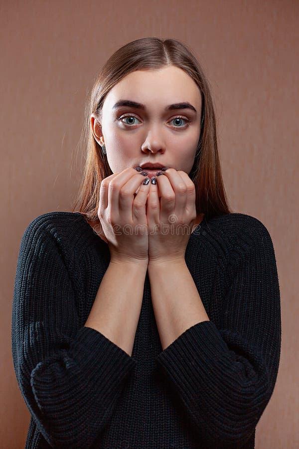 Mooie jonge vrouw met een uitdrukking van vrees, op een beige achtergrond stock foto