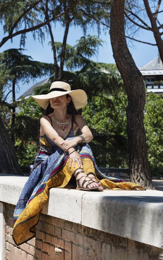 Mooie jonge vrouw met een zitting van de strohoed bovenop een muur in het park stock afbeelding