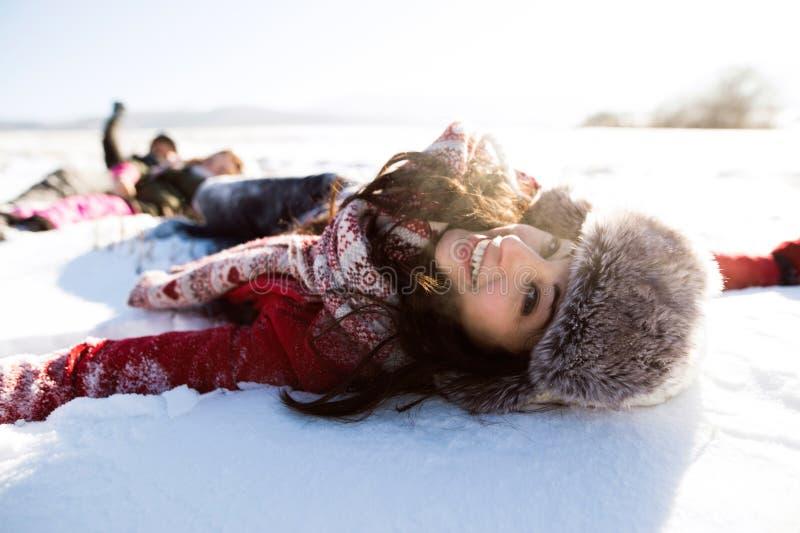Mooie jonge vrouw met familie, die pret in de sneeuw hebben stock foto's