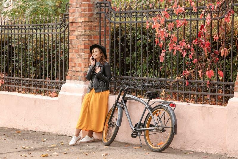 Mooie jonge vrouw met fiets die op mobiele telefoon in openlucht spreken royalty-vrije stock afbeeldingen