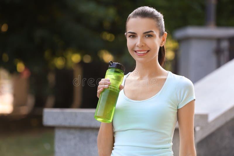 Mooie jonge vrouw met fles die water na opleiding in park rusten royalty-vrije stock foto's