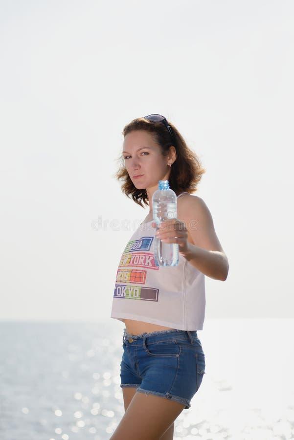 Mooie jonge vrouw met fles water stock foto