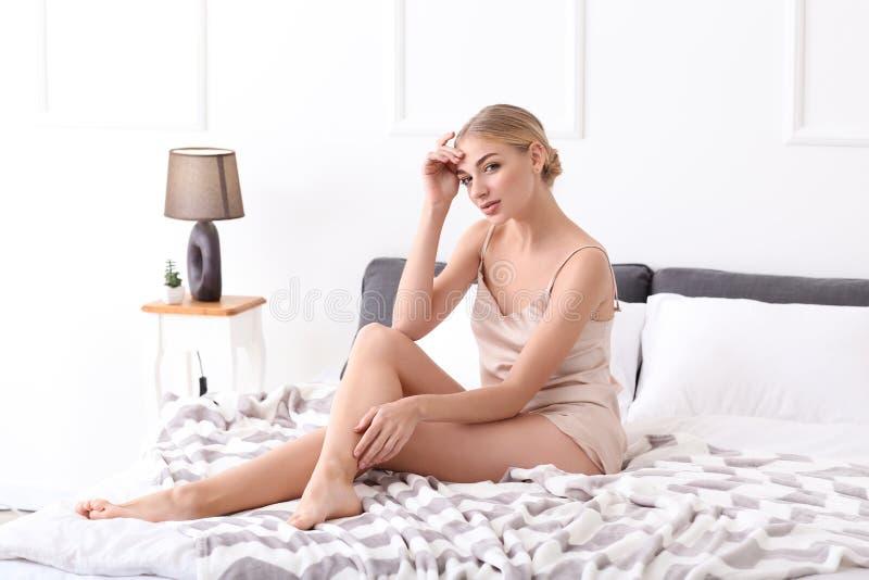 Mooie jonge vrouw met geschoren benen in slaapkamer royalty-vrije stock fotografie