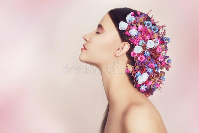 Mooie jonge vrouw met gevoelige bloemen in hun haar Schoonheidsmeisje met bloemenkapsel Modelportret met de Zomerroze royalty-vrije stock afbeelding