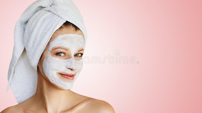 Mooie jonge vrouw met gezichtsmasker op haar gezicht Huidzorg en behandeling, kuuroord, natuurlijk schoonheid en de kosmetiekconc stock afbeeldingen