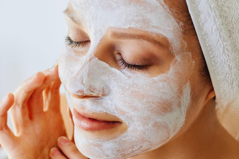 Mooie jonge vrouw met gezichtsmasker op haar gezicht Huidzorg en behandeling, kuuroord, natuurlijk schoonheid en de kosmetiekconc royalty-vrije stock afbeeldingen