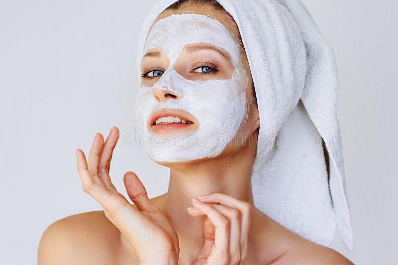 Mooie jonge vrouw met gezichtsmasker op haar gezicht Huidzorg en behandeling, kuuroord, natuurlijk schoonheid en de kosmetiekconc stock afbeelding