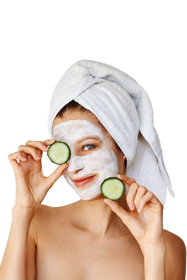 Mooie jonge vrouw met gezichtsmasker op haar plakken van de gezichtsholding van komkommer Huidzorg en behandeling, kuuroord, natu royalty-vrije stock fotografie