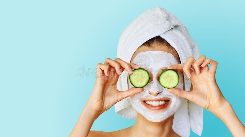 Mooie jonge vrouw met gezichtsmasker op haar plakken van de gezichtsholding van komkommer Huidzorg en behandeling, kuuroord, natu stock afbeeldingen