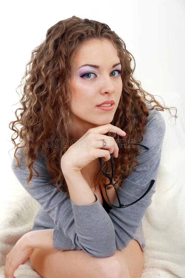Mooie jonge vrouw met glazen in grijze zitting stock afbeelding