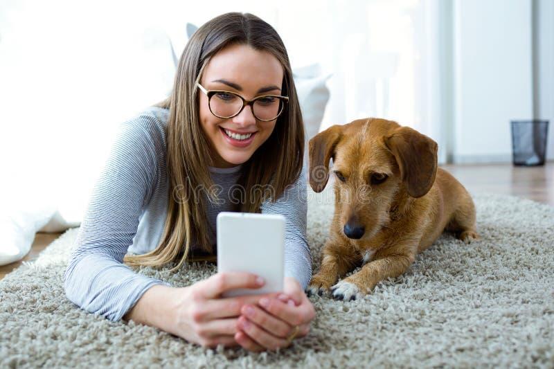 Mooie jonge vrouw met haar hond die mobiele telefoon thuis met behulp van royalty-vrije stock foto