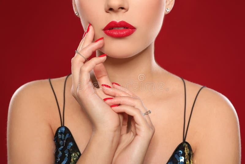Mooie jonge vrouw met heldere manicure op kleurenachtergrond Nagellaktendensen stock foto's