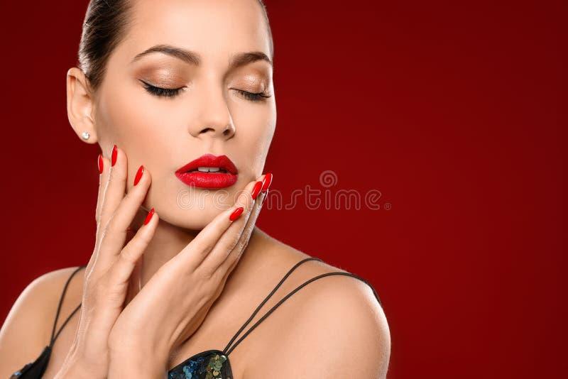 Mooie jonge vrouw met heldere manicure op kleurenachtergrond Nagellaktendensen royalty-vrije stock afbeelding