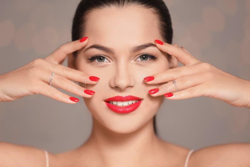 Mooie jonge vrouw met heldere manicure op vage achtergrond Nagellaktendensen royalty-vrije stock afbeelding