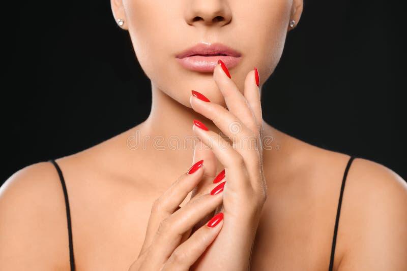 Mooie jonge vrouw met heldere manicure op zwarte achtergrond Nagellaktendensen royalty-vrije stock foto's