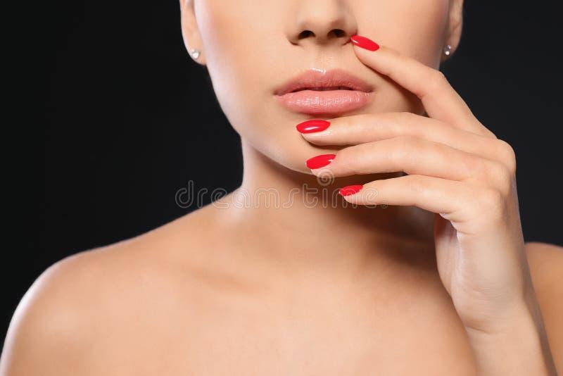 Mooie jonge vrouw met heldere manicure op zwarte achtergrond Nagellaktendensen stock fotografie