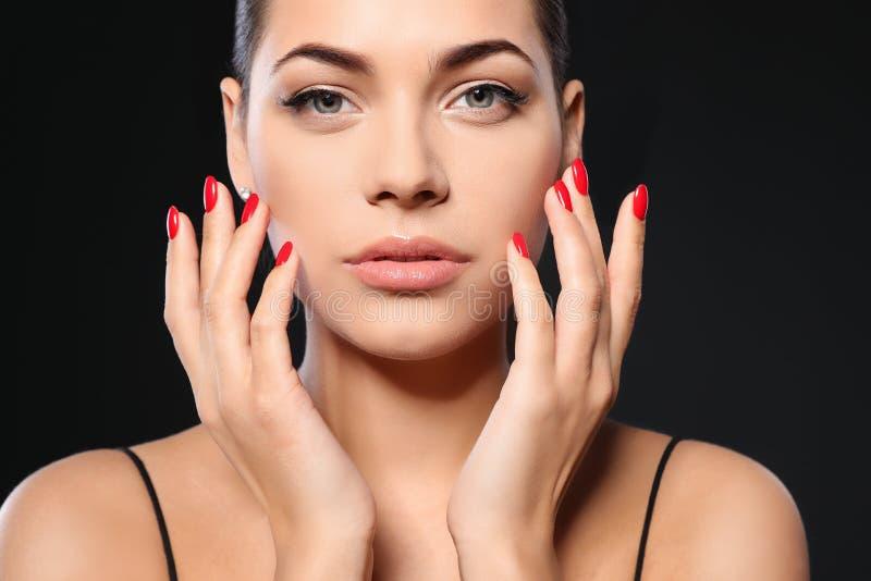 Mooie jonge vrouw met heldere manicure op zwarte achtergrond Nagellaktendensen royalty-vrije stock foto