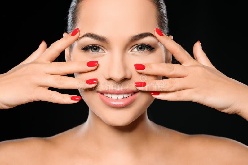 Mooie jonge vrouw met heldere manicure op zwarte achtergrond Nagellaktendensen royalty-vrije stock fotografie