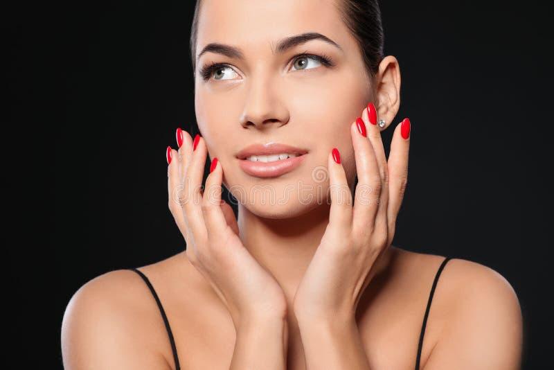 Mooie jonge vrouw met heldere manicure op zwarte achtergrond Nagellaktendensen royalty-vrije stock afbeeldingen