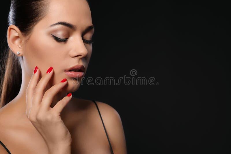 Mooie jonge vrouw met heldere manicure op zwarte achtergrond Nagellaktendensen royalty-vrije stock afbeelding