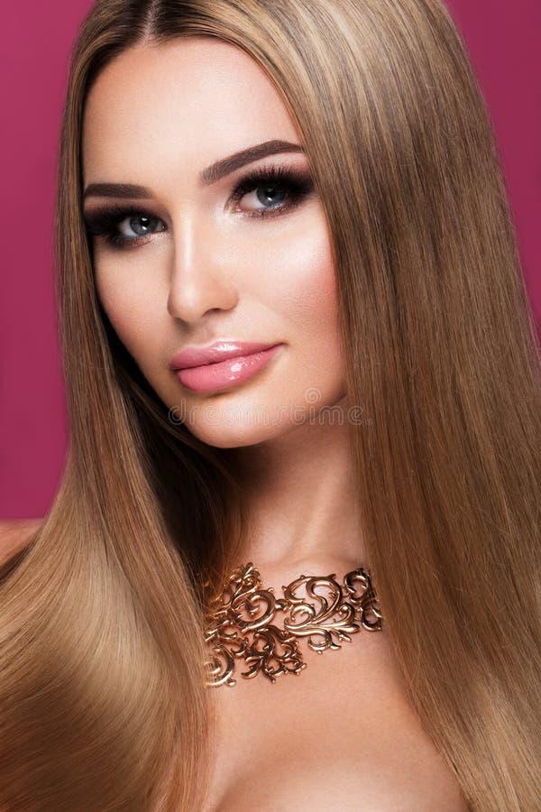 Mooie jonge vrouw met het lange haar stellen op roze glanzende achtergrond stock foto's