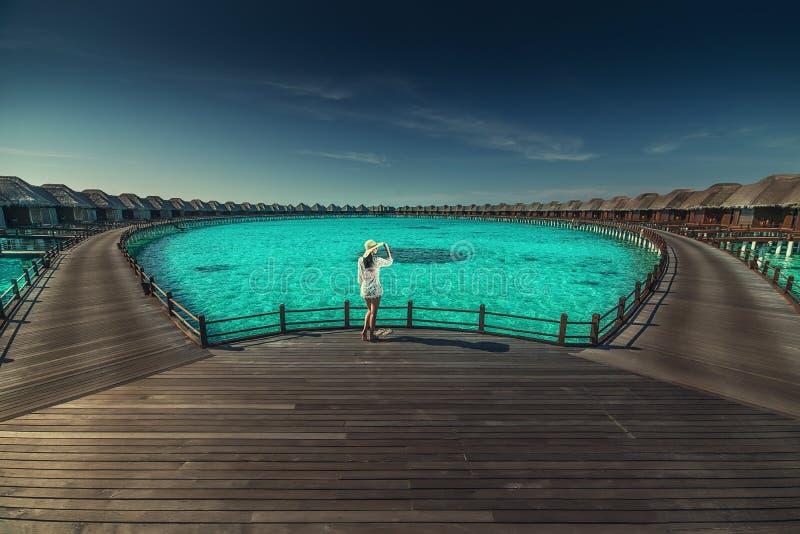 Mooie jonge vrouw met hoed op wit strand, mooi landschap met vrouw in de Maldiven, tropisch paradijs stock afbeelding