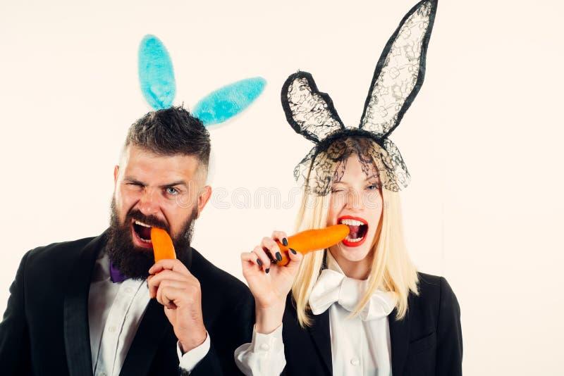 Mooie jonge vrouw met konijntjesoren en lege affiche op kleurenachtergrond Klaar voor de partij Gelukkige Pasen stock foto's