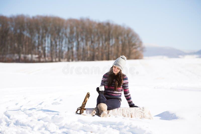 Mooie jonge vrouw met kop van koffie in de winteraard stock foto
