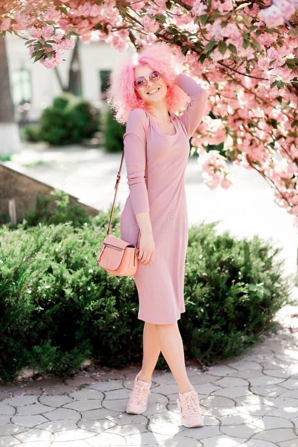 Mooie jonge vrouw met krullend roze haar en zonnebril dichtbij de tot bloei komende de lenteboom stock afbeelding