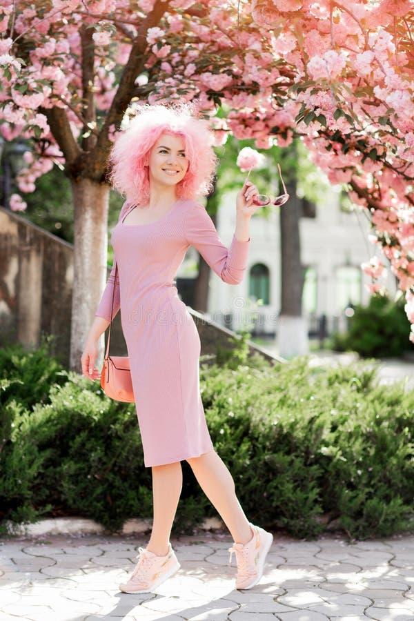 Mooie jonge vrouw met krullend roze haar en zonnebril dichtbij de tot bloei komende de lenteboom stock afbeeldingen