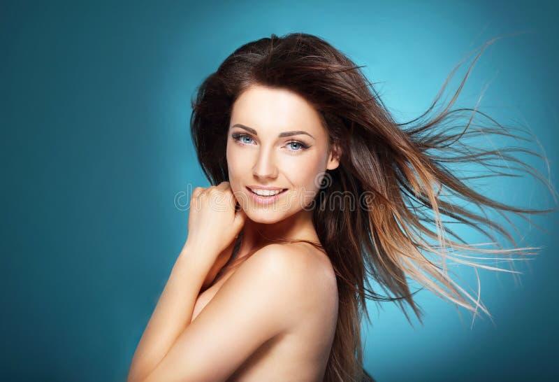Mooie jonge vrouw met lang bruin vliegend haar op blauwe backg royalty-vrije stock fotografie