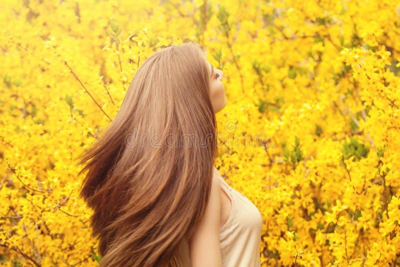 Mooie jonge vrouw met lang gezond haar tegen gele bloemenachtergrond Meisje met het blazen kapselportret stock fotografie