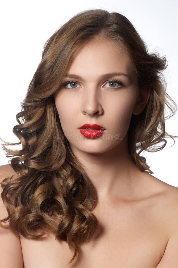 Mooie jonge vrouw met lang krullend haar Mooi modelverstand stock foto