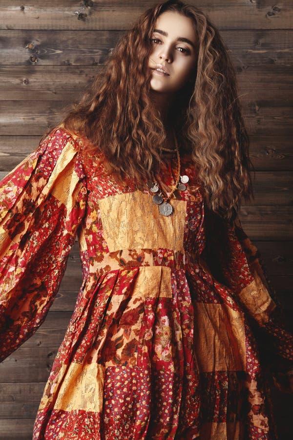 Mooie jonge vrouw met lang krullend kapsel, manierjuwelen met donkerbruin haar De Indische stijlkleren, snakken kleding royalty-vrije stock foto
