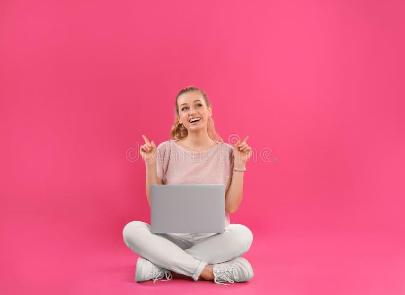 Mooie jonge vrouw met laptop op roze stock afbeelding