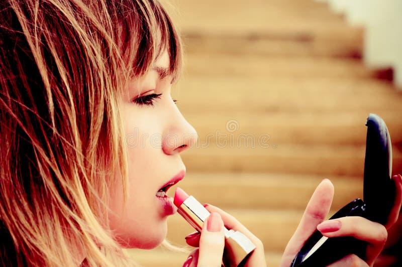 Mooie jonge vrouw met lippenstift en spiegel stock afbeeldingen